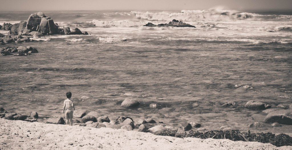 Little boy looking out at the giant waves