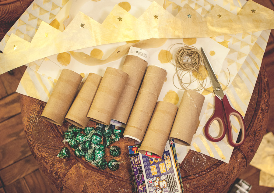 Materials: cardboard tubes, wrapping paper, paper crowns, scratch tickets, chocolates, and twine